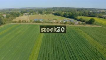Drone Shot Flying Backwards Over Farm Fields Of Crops, UK