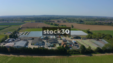 Drone Shot Flying Backwards Over Farm Buildings And Fields Of Crops, UK