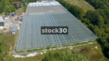 Rotating Anticlockwise Drone Shot Of Large Greenhouses On Farm, UK