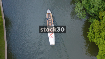 Overhead Drone Shot Of Cruise Boat Travelling Down The River Avon In Stratford, UK