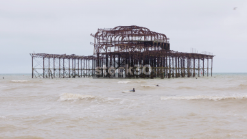 Burnt Out Brighton Pier On Overcast Day With Surfers In Water, UK