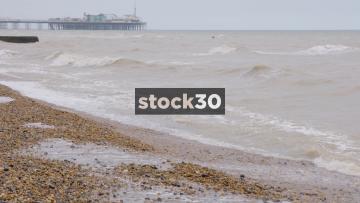 Waves Washing On Pebble Beach, Brighton Palace Pier In Background, UK