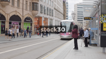 Tram Arrives And People Board On Corporation Street In Birmingham, UK