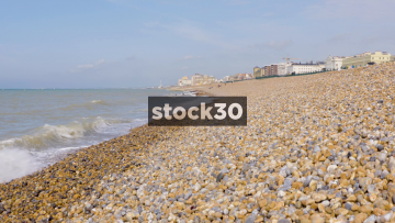 View Down Brighton Beach With Waves Lapping On Pebbles, UK