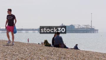 People Sitting On Brighton Beach, Brighton Palace Pier In Background, UK