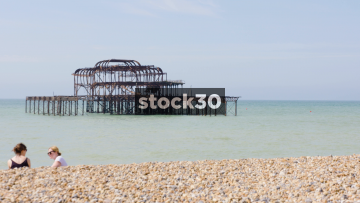 Burnt Out Pier In Brighton With Boat Sailing Past In Background, UK
