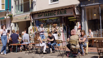 People Sitting At Tables Outside Cafe On Gardner Street In Brighton, UK