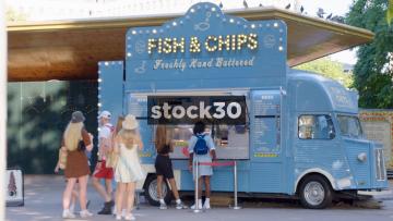 People Queuing At Fish & Chips Van In London, UK