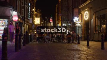 People Sitting Outside Bars On Rupert Street In Soho, London, At Night, UK