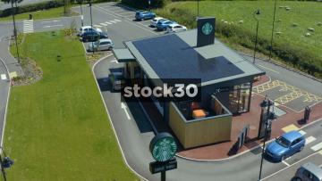 Drone Shot Orbiting Clockwise Around Starbucks Drive Thru With Solar Panels On Roof In Fylde, Lancashire, UK