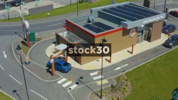 Drone Shot Orbiting Clockwise Around Burger King Drive Thru With Solar Panels On Roof In Fylde, Lancashire, UK