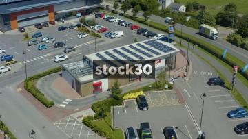 Drone Shot Orbiting Clockwise Around KFC Drive Thru In Fylde, Lancashire With Solar Panels On Roof, UK
