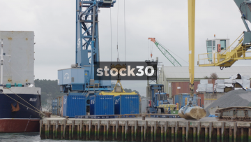 Crane Loading A Shipping Container Onto A Boat In Poole Harbour, UK